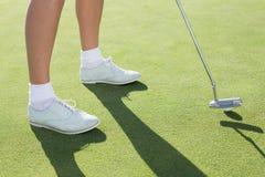 Golfista de la señora en el putting green Imagenes de archivo