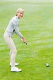 Golfista de la señora en el putting green Imagen de archivo