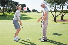 Golfista de la señora en el putting green en el décimo octavo agujero con el socio Fotografía de archivo libre de regalías