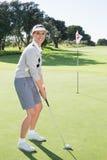 Golfista de la señora en el putting green en el décimo octavo agujero que sonríe en la cámara Foto de archivo