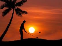 Golfista de la silueta que golpea el tiro de golf en puesta del sol Foto de archivo