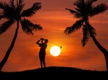 Golfista de la silueta que golpea el tiro de golf en puesta del sol Fotos de archivo
