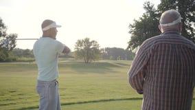 Golfista de Oriente Medio hermoso que balancea y que golpea la pelota de golf en curso hermoso Un más viejo hombre mira a su opos metrajes