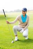 Golfista de sexo femenino kneeing en el putting green Fotografía de archivo libre de regalías