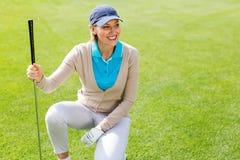 Golfista de sexo femenino kneeing en el putting green Imagen de archivo