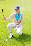 Golfista de sexo femenino kneeing en el putting green Fotografía de archivo