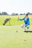 Golfista de sexo femenino que mira su bola en putting green Fotos de archivo