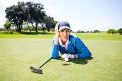 Golfista de sexo femenino que mira su bola en putting green Fotografía de archivo libre de regalías