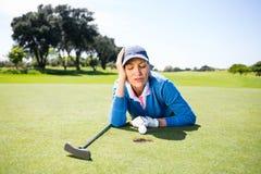 Golfista de sexo femenino que mira su bola en putting green Foto de archivo