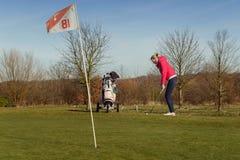 Golfista de sexo femenino que salta la pelota de golf en la taza con la bandera Foto de archivo libre de regalías