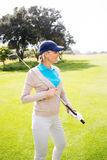 Golfista de sexo femenino que se coloca que celebra su sonrisa del club Fotos de archivo libres de regalías