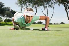 Golfista de sexo femenino que sopla su bola en putting green Fotografía de archivo libre de regalías