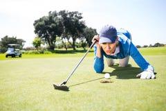Golfista de sexo femenino que sopla su bola en putting green Foto de archivo libre de regalías