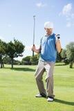 Golfista emocionado que anima en putting green Foto de archivo libre de regalías