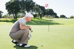 Golfista en el putting green en el décimo octavo agujero Imagen de archivo