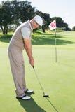 Golfista en el putting green en el décimo octavo agujero que sonríe en la cámara Fotos de archivo libres de regalías