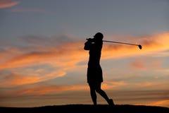 Golfista en la puesta del sol. Imágenes de archivo libres de regalías
