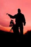 Golfista en la puesta del sol lista para jugar Foto de archivo