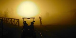 Golfista en la salida del sol de oro Imágenes de archivo libres de regalías