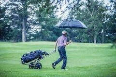 Golfista en un día lluvioso que sale del campo de golf Fotos de archivo libres de regalías