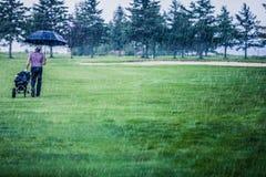 Golfista en un día lluvioso que sale del campo de golf Imagenes de archivo