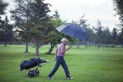 Golfista en un día lluvioso que sale del campo de golf Imagen de archivo