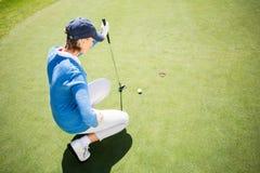 Golfista enfocado de la señora que se arrodilla en el putting green Fotografía de archivo