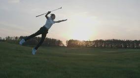 Golfista feliz del muchacho Muchacho menor alegre en el campo de golf en la puesta del sol metrajes