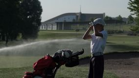 Golfista feliz del muchacho Muchacho menor alegre en el campo de golf en la puesta del sol almacen de metraje de vídeo