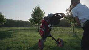 Golfista feliz del muchacho Muchacho menor alegre en el campo de golf en la puesta del sol almacen de video