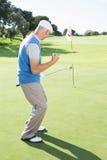 Golfista feliz que anima en putting green en el décimo octavo agujero Imagenes de archivo
