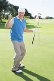 Golfista feliz que anima en putting green en el décimo octavo agujero Foto de archivo libre de regalías