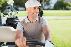 Golfista feliz que conduce el suyo cochecillo del golf fotografía de archivo