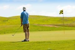 Golfista joven en verde que pone Imagenes de archivo