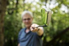 Golfista mayor que sostiene un palillo del club de golf foto de archivo libre de regalías