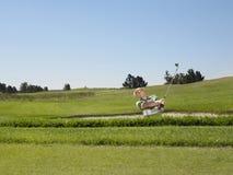 Golfista que balancea en trampa de arena Imagenes de archivo