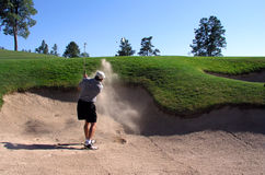 Golfista que golpea fuera de un desvío de arena Foto de archivo