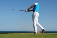 Golfista que golpea la bola con la fuerza Imagenes de archivo