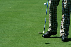 Golfista que hace juegos malabares una pelota de golf con los pantalones retros Fotos de archivo libres de regalías