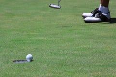Golfista que hunde un putt largo Imágenes de archivo libres de regalías