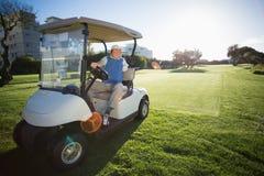 Golfista que invierte el suyo cochecillo del golf imagenes de archivo