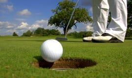 Golfista que pone la bola en el agujero imágenes de archivo libres de regalías
