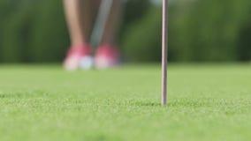 Golfista que pone la pelota de golf para agujerear El jugador que juega en campo de golf en puesta del sol es naturaleza hermosa