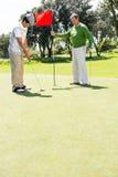Golfista que sostiene la bandera del agujero para el amigo que pone la bola Fotografía de archivo