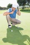 Golfista serio que se arrodilla en el putting green Fotografía de archivo libre de regalías