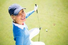Golfista sonriente de la señora que se arrodilla en el putting green fotos de archivo