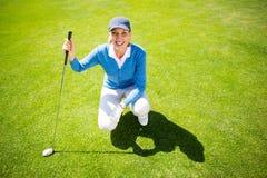 Golfista sonriente de la señora que se arrodilla en el putting green Foto de archivo libre de regalías