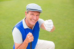 Golfista sonriente que se arrodilla en el putting green Foto de archivo