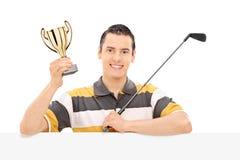Golfista trzyma trofeum za pustym panelem Fotografia Stock