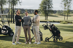 Golfistas con los clubs de golf que hablan y que pasan el tiempo junto en campo de golf imágenes de archivo libres de regalías